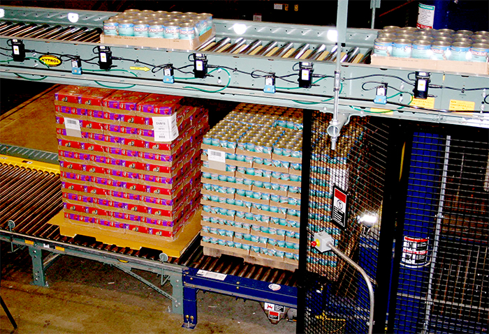 heavy pallet load of cans moving on a powered conveyor line